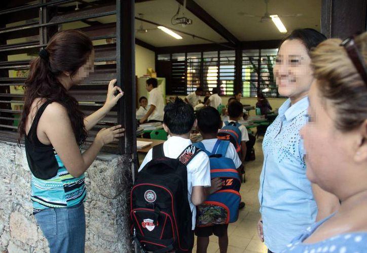 Los hombres tienen más acceso a la educación que las mujeres. Imagen de un grupo de mujeres en la puerta de un salón de clases. (Milenio Novedades)
