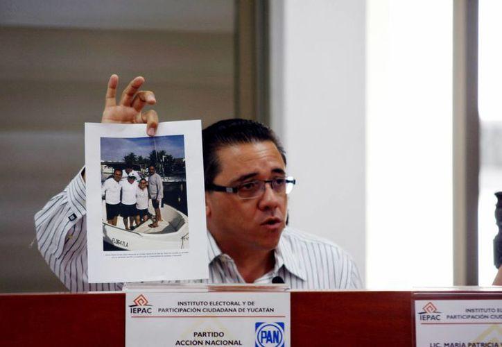 El diputado Víctor Hugo Lozano Poveda exhibe una foto con supuestas pruebas de los nexos con priistas del consejero Carlos Pavón Durán. (Christian Ayala/SIPSE)