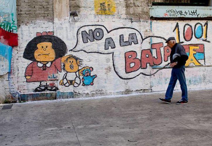 Un hombre pasa frente a una barda en la que aparecen los personajes Mafalda y Guille, utilizados en una campaña para bajar la edad criminal. Este domingo, los uruguayos eligen al próximo presidente del país. La imagen es de contexto. (AP)