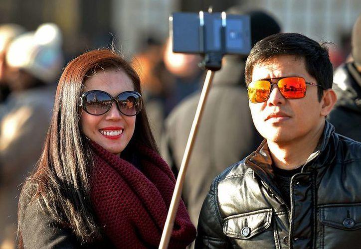 Turistas se toman una selfie en Londres. Los brazos extensibles que se requieren para este tipo de fotos no podrán ser utilizados en importantes festivales musicales en EU por razones de seguridad. (Foto de archivo de AP)