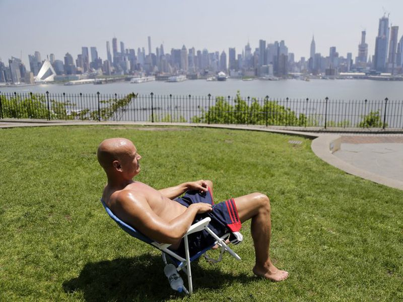 Rick Stewart sits in the sunshine with the New York City skyline in the background, in a park in Weehawken, N.J. (AP)