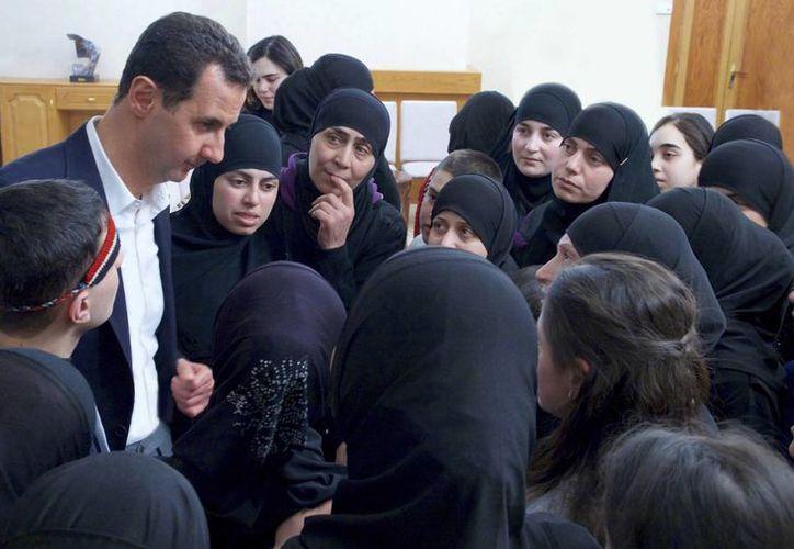 Imagen del presidente Bashar Assad al reunirse con ex rehenes liberados en un intercambio de prisioneros con los rebeldes, en Damasco, Siria. (SANA vía AP)