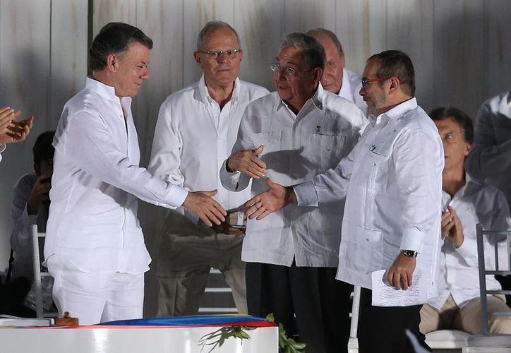 Imagen del comandante de las FARC Rodrigo Londoño (d), estrecha la mano del presdidente Juan Manuel Santos,  tras firmar un acuerdo de paz entre el gobierno y la guerrilla en Cartagena, Colombia. (AP/Fernando Vergara)