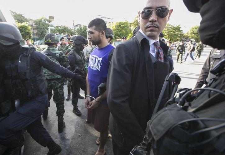 Agentes custodian a un sospechoso clave del ataque en Bangkok, identificado como Mierali Yusufu, luego de una reconstrucción del hecho. (Agencias)