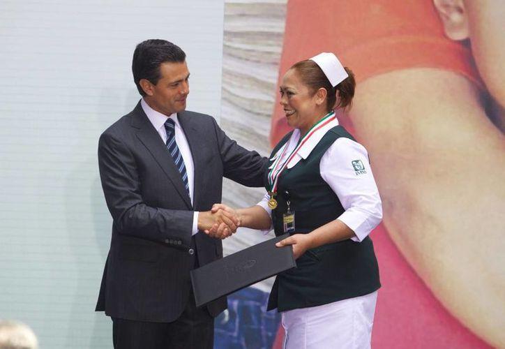El presidente Peña Nieto entrega un reconocimiento a una enfermera en el acto en que dio a conocer su Política Nacional de Salud, hoy en Palacio Nacional. (Notimex)