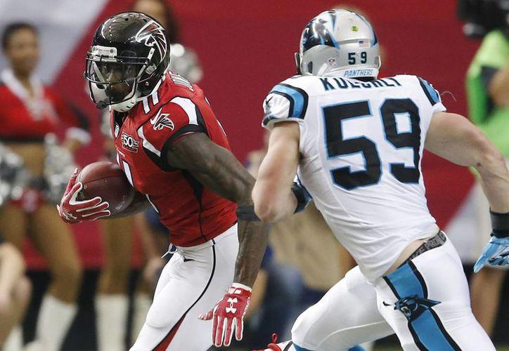 El receptor de los Halcones Julio Jones se escapa de la defensa de Carolina para apoyar la victoria de su equipo, 20-13 en juego de la semana 16 de la NFL. (AP)