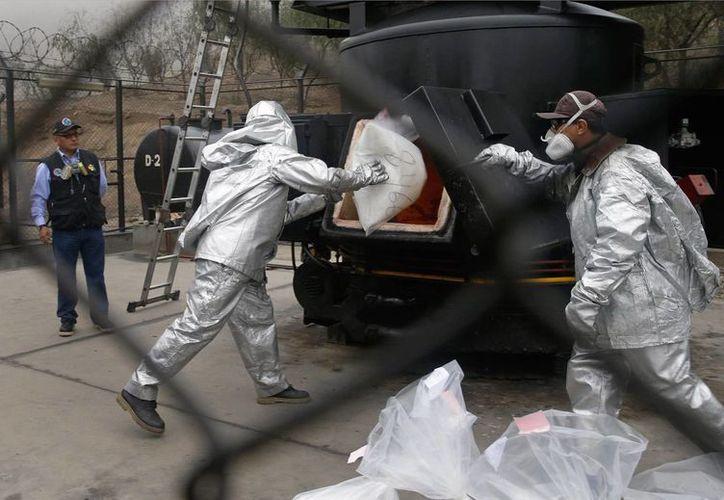 Con trajes especiales, trabajadores lanzan a un horno costales con cocaína para ser incinerados en un cuartel policial en Lima, Perú, el miércoles 3 de septiembre de 2014. (AP Photo/Martin Mejia)