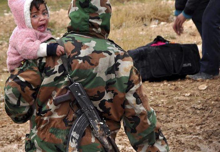 Fotografía distribuida por la agencia oficial siria SANA que supuestamente muestra a residente sirios mientras son evacuados de Adra, ayer, por soldados sirios, en el noreste de Damasco, Siria. (EFE)