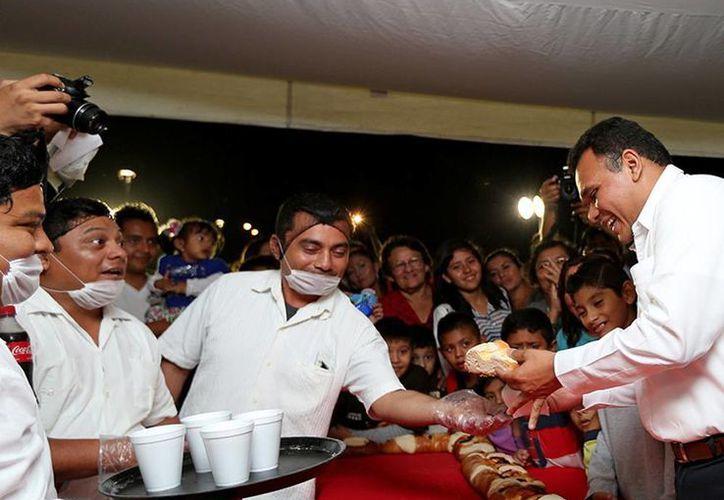 El gobernador de Yucatán, Rolando Zapata Bello, entregará obras de rehabilitación de arterias de Mérida. En la imagen, el mandatario corta la tradicional corte de la Rosca de Reyes.(Cortesía)