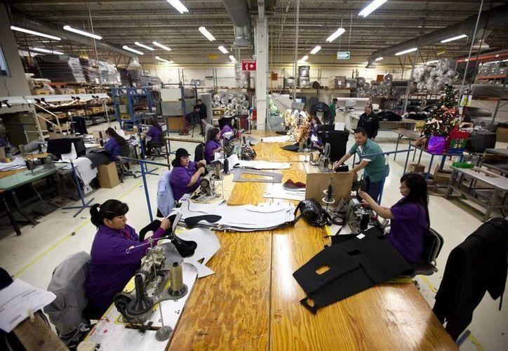El gobierno de Brasil aportará un subsidio de 300 dólares por empleado para que continúe en su puesto. Imagen de un grupo de trabajadores en una fábrica. (Archivo/SIPSE)