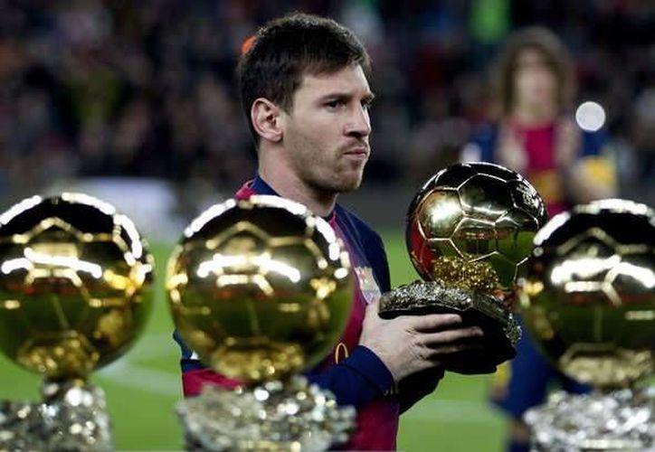 Messi con los cuatro Balones de Oro que ha ganado hasta ahora. (www.ole.com/Foto de archivo)