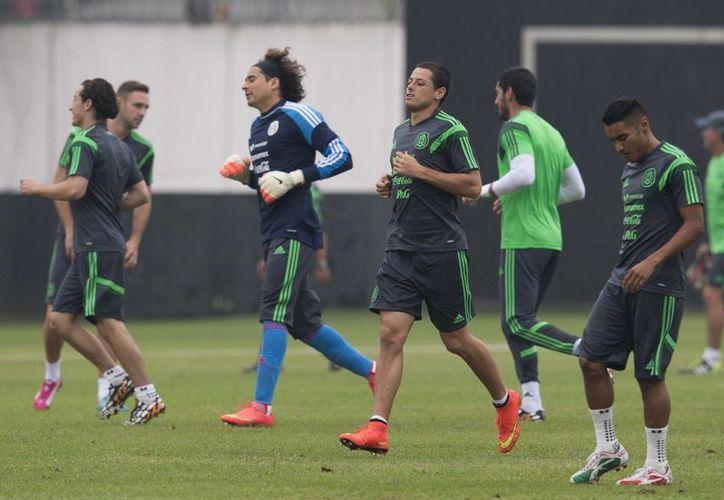 Guillermo Ochoa y 'Chicharito' Hernández (centro) durante un entrenamiento del Tri en Natal, Brasil, antes de debutar ante Camerún este viernes. (Notimex)