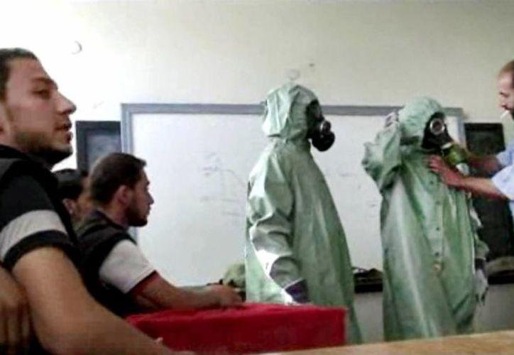 Imagen de un video que AP publicó el 18 de septiembre de 2013 y que muestra a un voluntario ajustando a un estudiante un traje y máscara antigases durante una sesión de cómo reaccionar ante ataques con armas químicas, en Alepo, Siria.(Foto AP/Archivo)