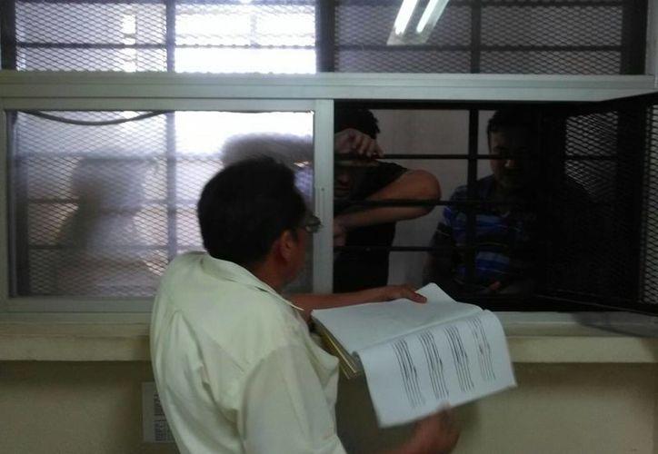 Momento en que dos de los acusados del fraude de Crecicuentas reciben la notificación de que continuará el proceso penal en su contra. (Milenio Novedades)