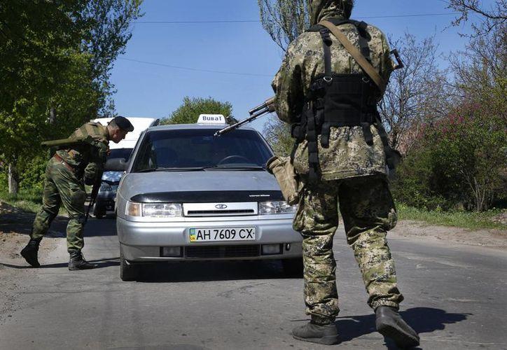 Prorrusos armados inspeccionan un vehículo cerca de Slovyansk, este de Ucrania. (Agencias)