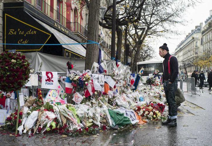 El cantante Jesse Hughes, líder del grupo estadounidense de rock Eagles of Death Metal, la banda que sonaba en la sala Bataclan de París cuando tres terroristas suicidas irrumpieron y mataron a 89 personas, rinden homenaje a las víctimas frente al simbólico local en la capital gala. (EFE/Archivo)