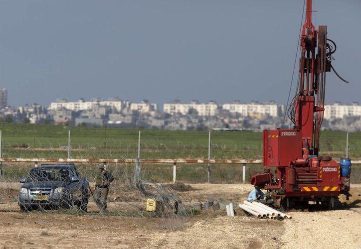 Empleados israelíes llevan a cabo perforaciones cerca de la localidad de Nir Am en Israel, para la detección de túneles. (EFE/Archivo)