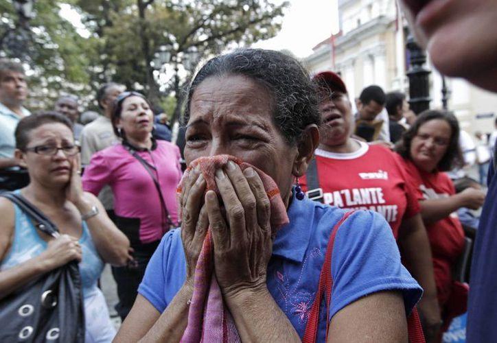 La televisión local mostró a simpatizantes del oficialismo llorando en las afueras del presidencial Palacio de Miraflores y del Hospital Militar. (Agencias)