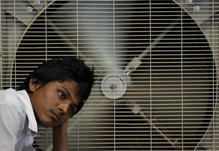 Un hombre descansa ante un ventilador para aliviar su calor en Hyderabad, India, país que alcanzó temperaturas de 45 grados. (Agencias)