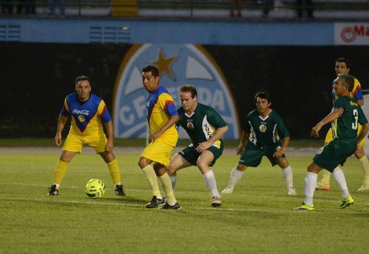 El capitán Jorge Esquivel Millet (centro) disputa el balón a los veteranos americanistas. (Luis Pérez/SIPSE)