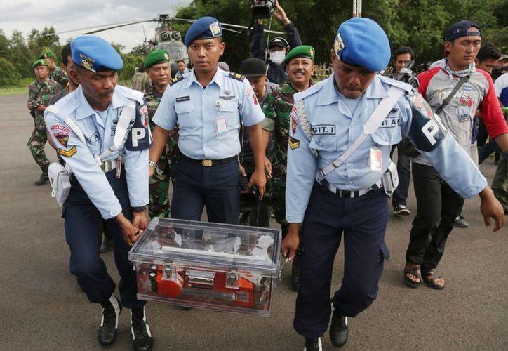 Personal militar transporta la primera 'caja negra' del avión de AirAsia que cayó en el mar, ayer, en Pangkalan Bun, Indonesia. Hoy, los buzos recuperaron la otra caja. (Foto: AP)
