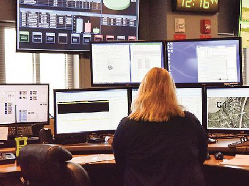 Adispatcher works at a desk station with a variety of screens used by those who take 911 emergency calls in Roswell, Ga.