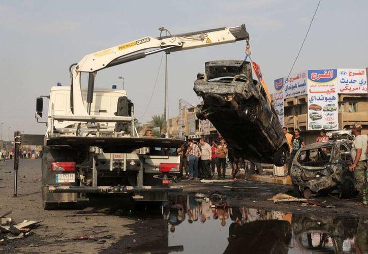 Ante la mirada de curiosos, una grúa se lleva los restos de uno de los varios automóviles que este jueves estallaron en diversos puntos de Bagdad. Al menos 35 personas murieron en diferentes ataques. (AP)