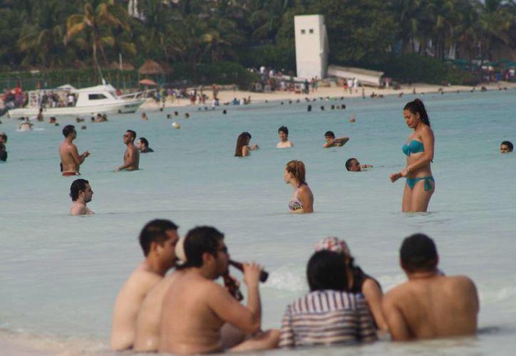 En las playas de la Riviera Maya la afluencia de personas es positiva, pues turistas aprovechan para tomar el sol o sumergirse en el agua. (Octavio Martínez/SIPSE)