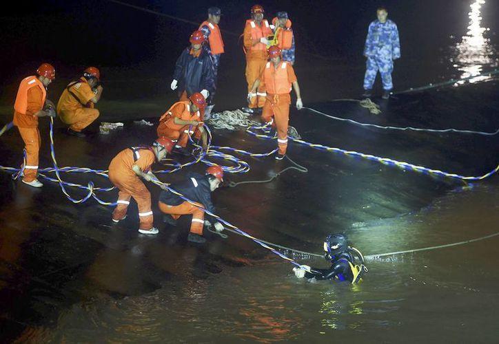 Imagen proporcionada por la agencia china Xinhua donde se ve a rescatistas que trabajan en el naufragio de un crucero en el río Yangtsé. Cada momento se desvanecen las esperanzas de rescatar a más de 400 personas atrapadas en lo que podría convertirse en el accidente con más muertos en aguas chinas.(Agencias/AP)