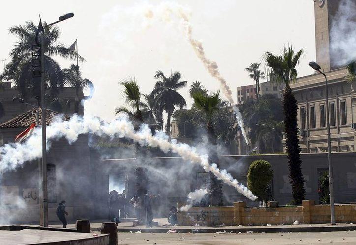 Soldados antidisturbios egipcios lanzan gas lacrimógeno durante los enfrentamientos con seguidores de los simpatizantes de los Hermanos Musulmanes cerca de la universidad de El Cairo, Egipto. (Archivo/EFE)