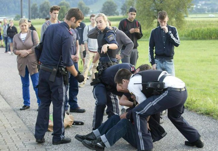 Momento en que el atacante es detenido por la policía, tras apuñalar a dos jóvenes. (AFP)