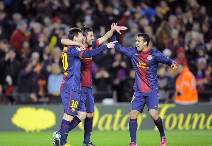 Messi (i) es felicitado por Villa y Pedro tras anotar. (AP)