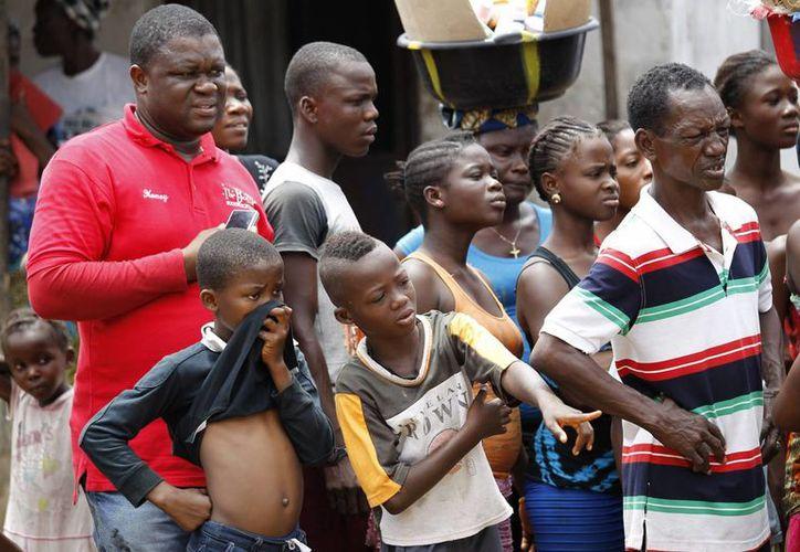 Unas personas gesticulan al ver el traslado de un cadáver de una persona que falleció, supuestamente, a causa del ébola, en Monrovia, Liberia. (EFE/Archivo)