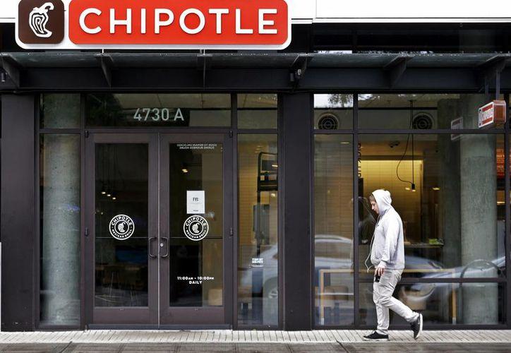 En imagen del 2 de noviembre de 2015, un hombre camina frente a un restaurante de la cadena Chipotle en Seattle, Washington, EU, cerrado por sospecha de un brote de E. coli, que fue descartado este lunes 9 de noviembre de 2015. (Archivo/AP)