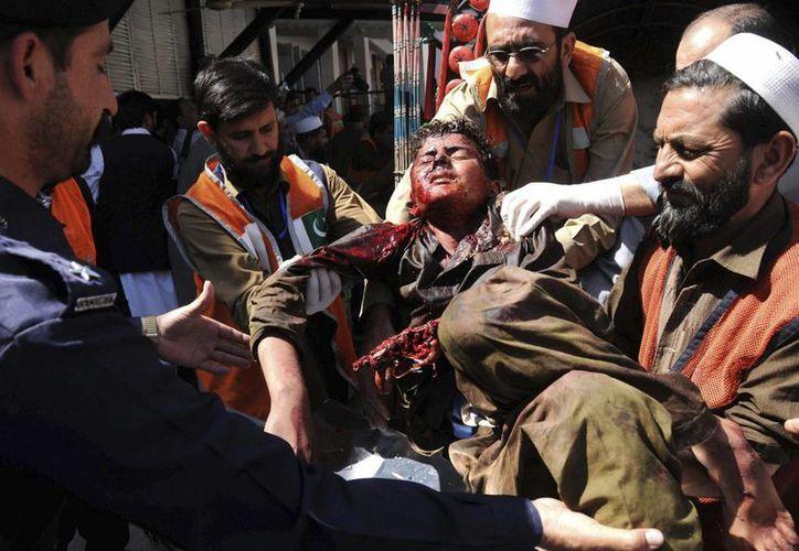 Miembros de los servicios de emergencia trasladan a un niño tras el atentado contra un campo de desplazados, a un hospital de Peshawar, Pakistán. (EFE)