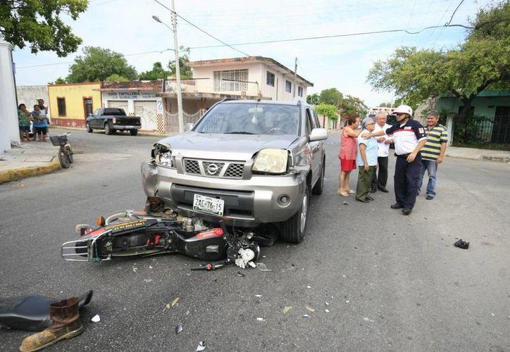 La moto en la que viajaban dos jóvenes quedó debajo de la camioneta conducida por una mujer de la tercera edad. (Jorge Sosa/SIPSE)
