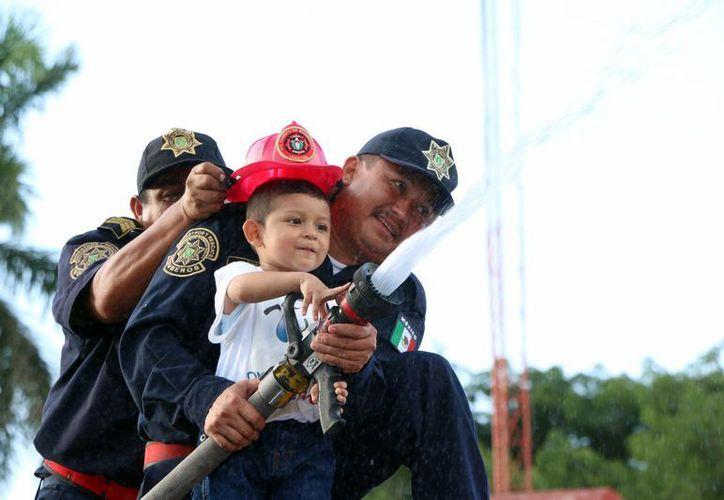 Gracias a Dr. Sonrisas y a la Secretaría de Seguridad Pública Milton Emanuel Dzib Pech pudo ser este jueves bombero por un día. (José Acosta/ Milenio Novedades)