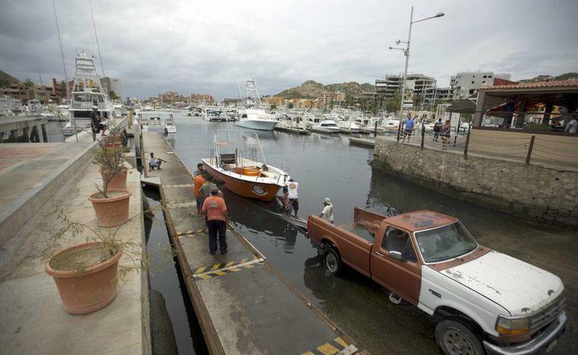 Residentes remolcan un bote para sacarlo del agua ante la llegada del huracán Newton en Cabo San Lucas. (AP/Eduardo Verdugo)