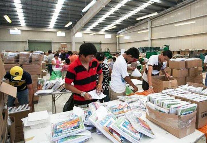 Voluntarios empaquetan los útiles escolares que se entregarán a miles de estudiantes próximamente. (Milenio Novedades)