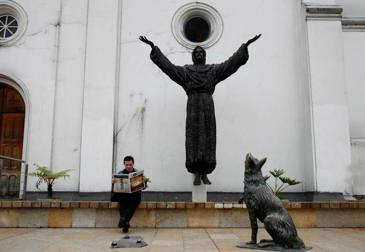 Un hombre lee en Bogotá, Colombia, un periódico junto una estatua de San Francisco de Asís, cuya biografía oficial se verá afectada debido al descubrimiento de un historiador. (EFE/Archivo)