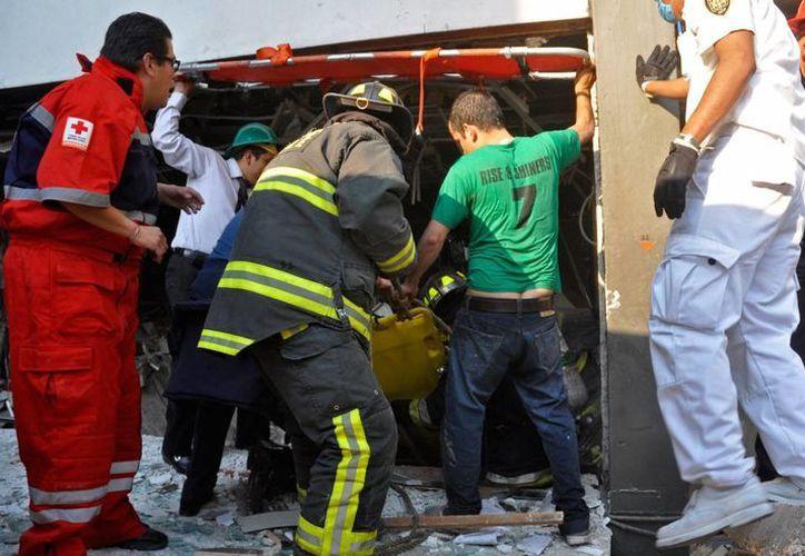 Continúan labores de remoción de escombros para detectar a más personas atrapadas. (AP)
