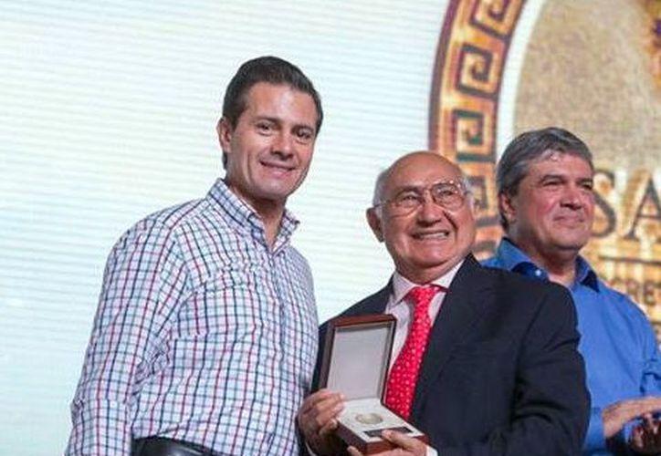 Abelardo Conde Medina recibe una presea de manos del presidente Enrique Peña Nieto. (Milenio Novedades)