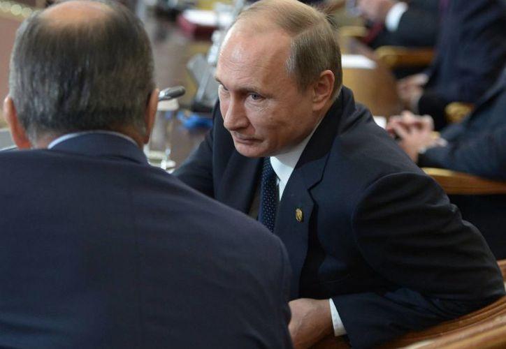 El presidente ruso Vladimir Putin (der), conversa con el canciller Serguei Lavrov, de espaldas a la cámara, durante una cumbre de la Comunidad de Estados Independientes. (Agencias)