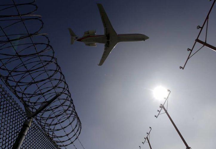 Un avión de pasajeros captado volando sobre la valla perimetral del aeropuerto internacional de Los Angeles, California, antes de aterrizar. (Agencias)