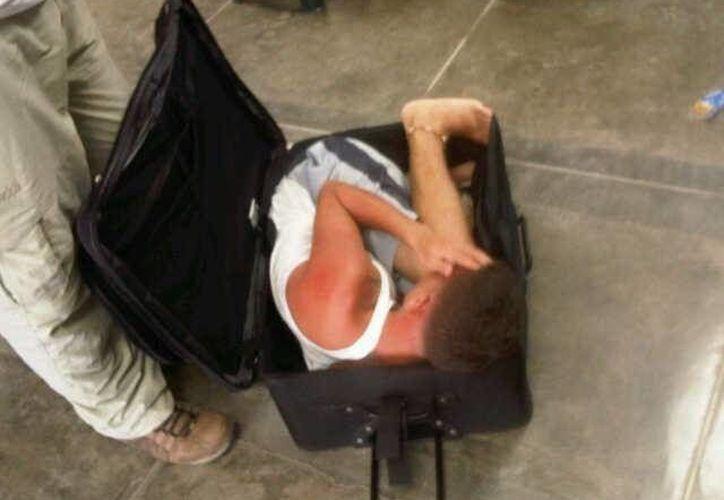 Gavinson García escondido en la maleta dentro de la cual pretendía escapar. (EFE)