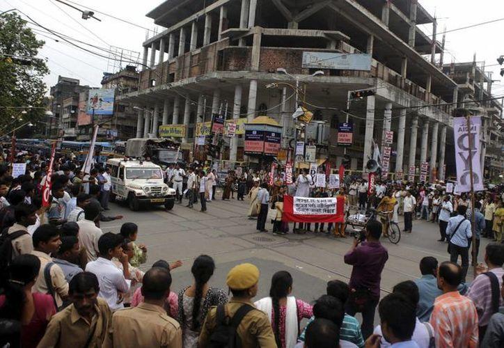 Ciudadanos indios gritan consignas durante una protesta convocada tras la violación en grupo de una niña de 16 años en Calcuta. (Archivo/EFE)
