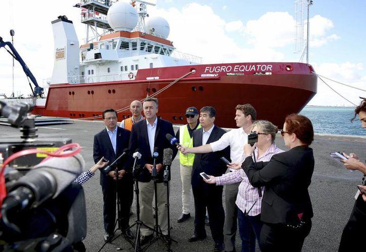 El ministro australiano de Infrastructura y Transporte, Darren Chester (tercero por la izquierda), ofrece una rueda de prensa, en Perth, Australia, acompañado por su homólogo malasio Liow Tiong Lai (izq), y otros funcionarios, ante el buque de búsqueda Fugro Equator, uno de los buques implicados en la búsqueda del MH370. (Richard Wainwright/AAP Image via AP)