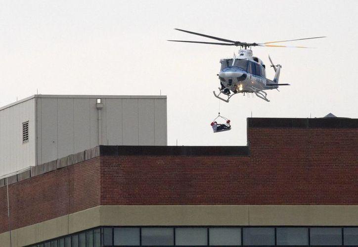A través de un helicóptero las autoridades rescatan a una persona del edificio naval donde ocurrió la balacera. (Agencias)