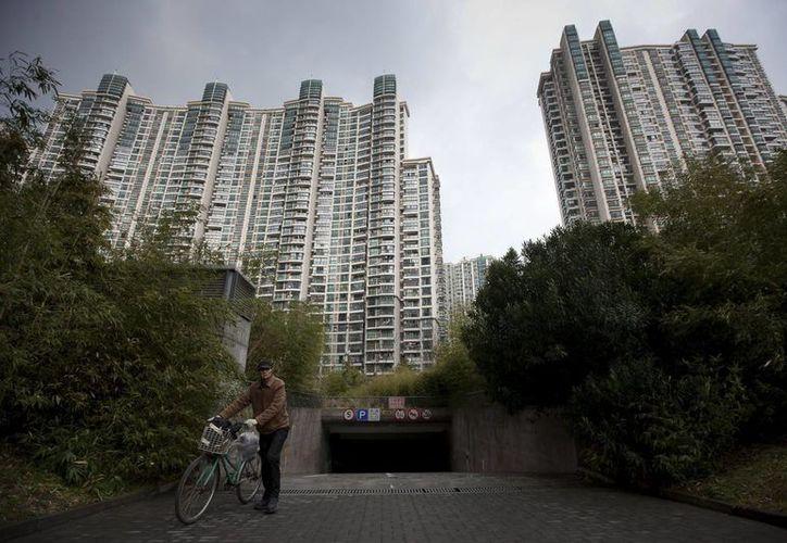 Un hombre empuja su bicicleta por las calles de una zona residencial en Shangai, China. (Archivo/EFE)