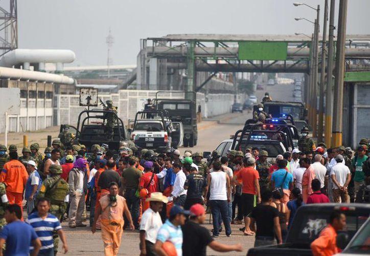 Habitantes de Mundo Nuevo marcharon hacia los accesos de la planta Clorados III, de Pemex, en Coatzacoalcos, para exigir que les entreguen los cuerpos faltantes. (EFE)
